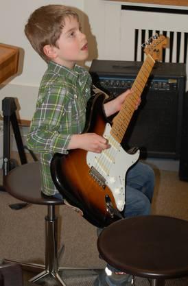 Adam versucht sich bei der Instrumentenwerkstatt auf der E-Gitarre.
