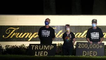 Die Demonstranten Mark Beaumont (l-r), Joyce Brown und Bruce Brown halten in der Nähe des Trump International Golf Club eine Mahnwache ab. In den USA sind inzwischen über 200 000 Menschen nach einer Corona-Infektion gestorben. Foto: Meghan Mccarthy/Palm Beach Post via ZUMA Wire/dpa