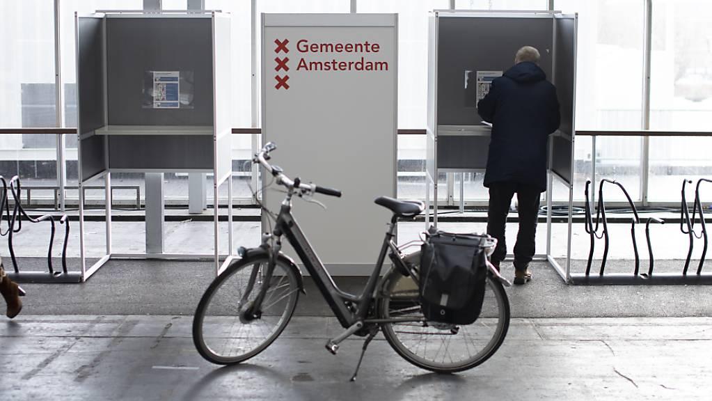 Ein Fahrrad steht vor Wahlkabinen, die neben Fahrradständern aufgebaut sind. Die Wahlen zum neuen niederländischen Parlament haben begonnen. Rund 13 Millionen Bürger sind aufgerufen, die 150 Abgeordneten der Zweiten Kammer zu wählen. Wegen der Corona-Pandemie wird die Parlamentswahl zum ersten Mal an insgesamt drei Tagen stattfinden.
