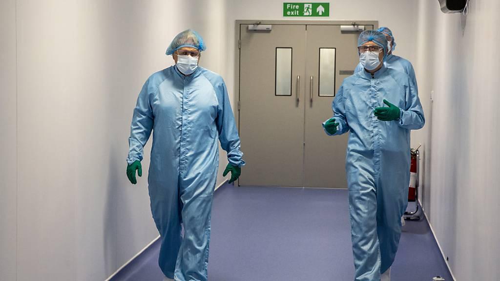 Boris Johnson (l), Premierminister von Großbritannien, geht mit Simon Simpkins, Produktionsleiter bei Oxford Biomedica, während eines Rundgangs durch die Produktionsanlage für den Corona-Impfstoff von Oxford/Astrazeneca bei Oxford Biomedica. Foto: Heathcliff O'malley/The Daily Telegram/PA Wire/dpa