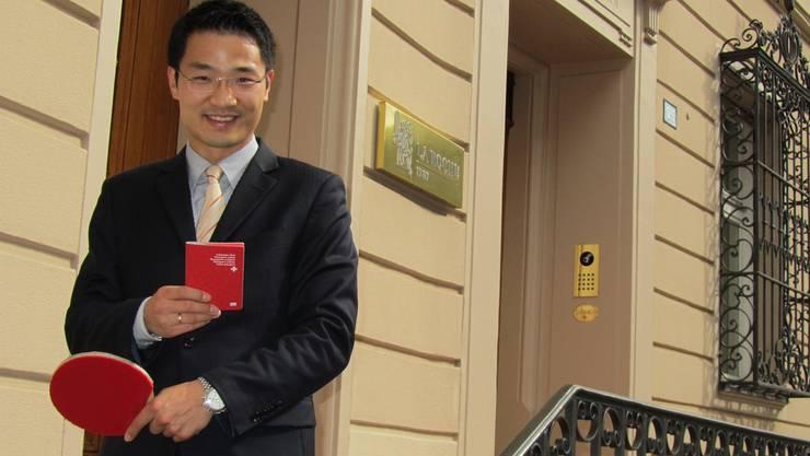 Jiashun Hu mit seinem Schläger und dem Schweizer Pass vor dem Hauptgebäude seines Arbeitgebers in der Basler Altstadt.
