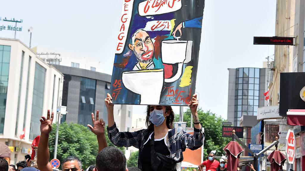 Ein tunesischer Demonstrant hält ein Plakat, auf dem Parlamentspräsident Rached Ghanouchi gemalt ist. Foto: Jdidi Wassim/SOPA Images via ZUMA Press Wire/dpa