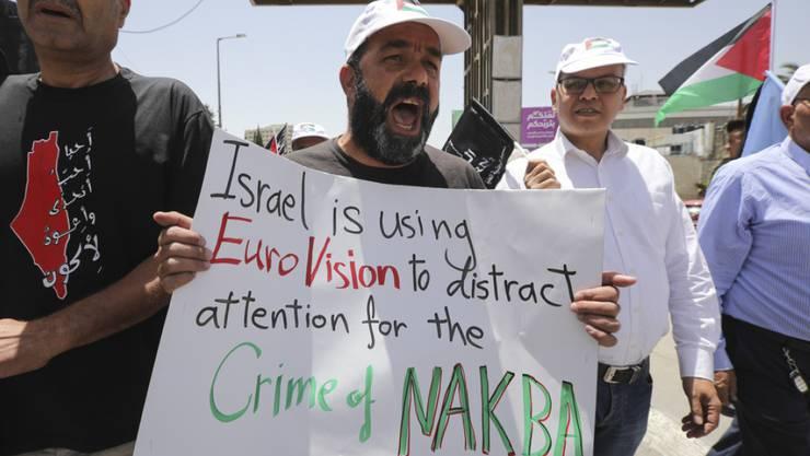 """""""Israel benutzt EuroVision, um vom Verbrechen der Nakba abzulenken"""" steht auf einem Plakat, mit dem Palästinenser an ihrem Tag der Katastrophe (Nakba) gegen den Eurovision Song Contest in Tel Aviv demonstrieren."""