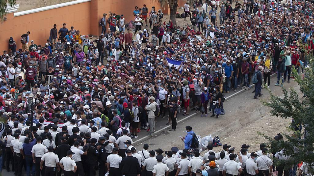 Migranten aus Honduras stehen vor Polizisten, die eine Straße blockieren. Foto: Sandra Sebastian/AP/dpa