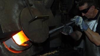 Ein Angestellter der Goldverarbeitungsfirma Argor-Heraeus füllt Rohgold in Formen ab. (Archiv)