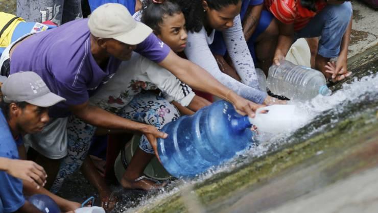 Prekäre Wasserversorgung in Venezuela wegen des Stromausfall: Menschen in der Hauptstadt Caracas holen sich Wasser bei einer leckgeschlagenen Leitung.