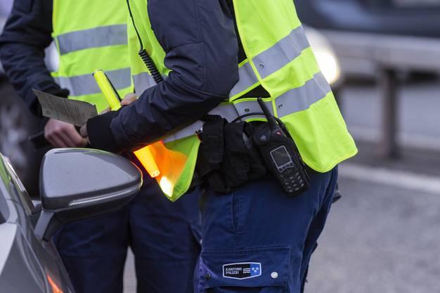 Die Polizisten kontrollieren auch Führer- und Fahrzeugausweis der Autofahrer.