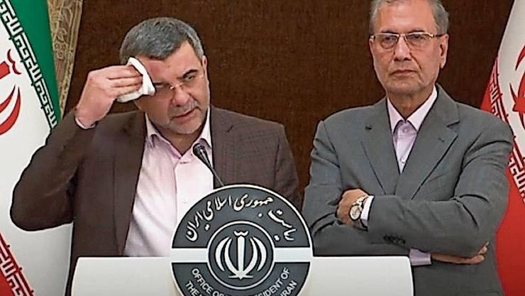 Der infizierte Vizegesundheitsminister Iraj Haririchi (l) wischt sich an einer Pressekonferenz den Schweiss von der Stirn.