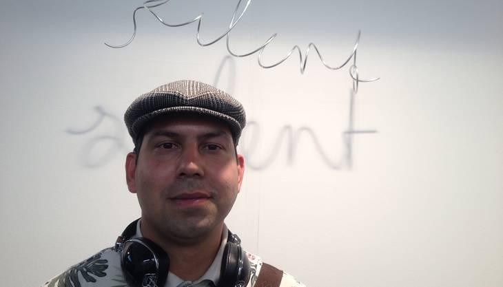 «Silent», still ist das Wort, das der Schatten eines Drahtgebildes wirft. Ein Kunstwerk in der Volta-Messe, das Jotham Bisang besonders inspirierend findet. Dass er die Stille an sich aber selten geniesst, darauf deutet der Kopfhörer hin, den er um den Hals trägt, Marke Skullcandy - was wiederum die Firma ist, bei der er als Grafiker arbeitet. Er sei zudem Strassenkünstler. «Jeder Künstler hört Musik, wenn er Kunst macht», sagt er. Vielleicht könne er seiner Firma nahe bringen, auch als Sponsorin von Künstlern und Kunstevents aufzutreten, bisher habe diese sich vor allem auf den Sportsektor konzentriert. Jotham (hebräisch für: Jehova hat es vollkommen gemacht) wünsche sich, dass Kunstmuseen und Messen in Zukunft so zugänglich, offen und eintrittsfrei sein werden wie Strassenkunst.