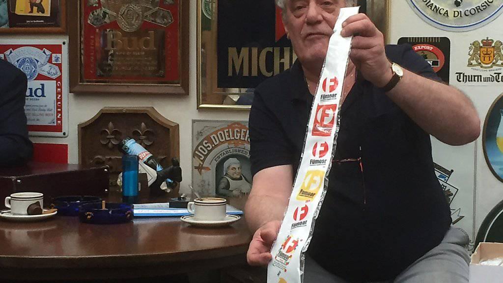 Der Präsident des Basler Raucherbeizen-Vereins «Fümoar», Mario Nanni, verschenkt die letzten übrig gebliebenen Vereinskrawatten an der Medienkonferenz zum Aus des Vereins - im unbedienten Fumoir seines Lokals.