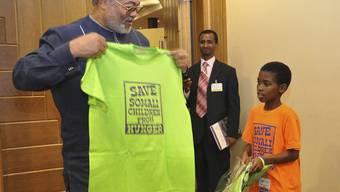 """Jerry Rawlings mit einem T-Shirt mit dem Aufdruck """"Rettet somalische Kinder vor dem Hungertod"""""""