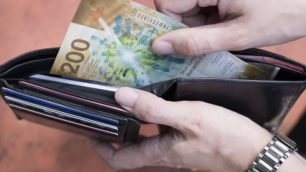 Negativzinsen für Kleinsparer sind wenig wahrscheinlich: Ein Mann mit einer 200-Franken-Note (Archivbild).
