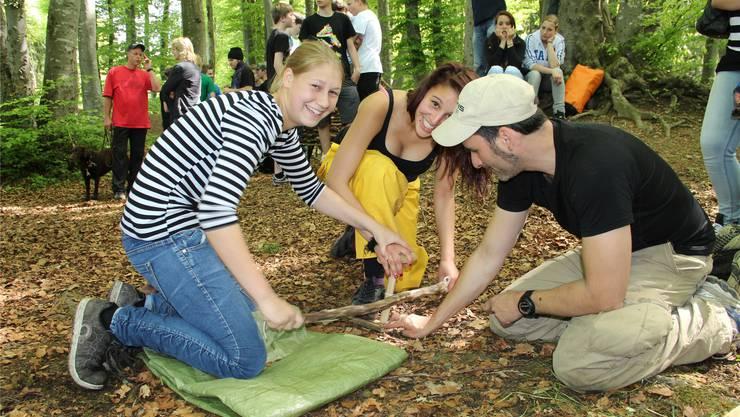 Evelyne (15) und Salima (16) versuchen unter Anleitung von Dario Carrozza nur mit Holz, einer Schnur und trockenem Gras ein Feuer zu machen.