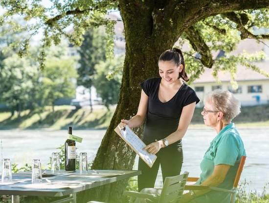 Tamara Bindt bedient einen Gast: Im Restaurant Brücke lässt sich etwas Wein lässt an der Aare geniessen.