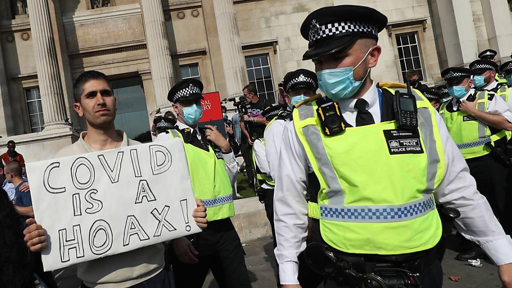 Ein Mann hält am Trafalgar Square bei einer Demonstration von Impfgegnern ein Schild mit der Aufschrift «Covid is a hoax» (Covid ist ein Schwindel) in die Höhe. Foto: Yui Mok/PA Wire/dpa