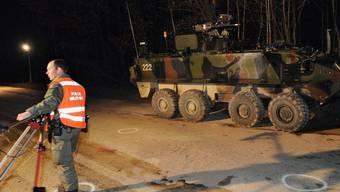Militärangehöriger untersucht einen in einen Unfall verwickelten Panzer des Typs Piranha an der Unglückstelle in Bure