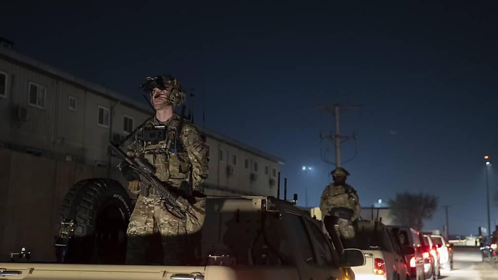 ARCHIV - Bewaffnete Soldaten stehen Wache in der Fahrzeugkolonne für Präsident Donald Trump, der während eines Überraschungsbesuchs am Thanksgiving Day bei den Truppen auf dem Bagram Air Field in Afghanistan spricht. Foto: Alex Brandon/AP/dpa