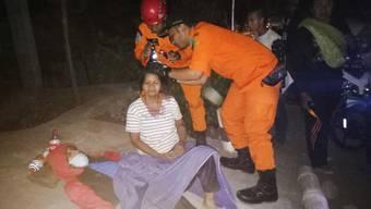 Schon wieder ein starkes Erdbeben auf Lombok: Ein Retter kümmert sich um eine verletzte Frau.