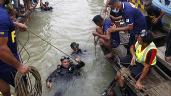 Taucher steigen nach einem Schiffsunglück für die Bergung von Opfern in den Fluss Buriganga. Foto: Str/Xinhua/dpa