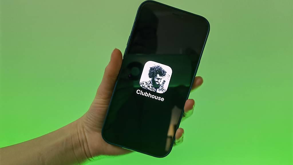 Eine Nutzerin der Social-Media-App Clubhouse zeigt ihr Smartphone mit dem Logo der Audio-Anwendung. Foto: Christoph Dernbach/dpa