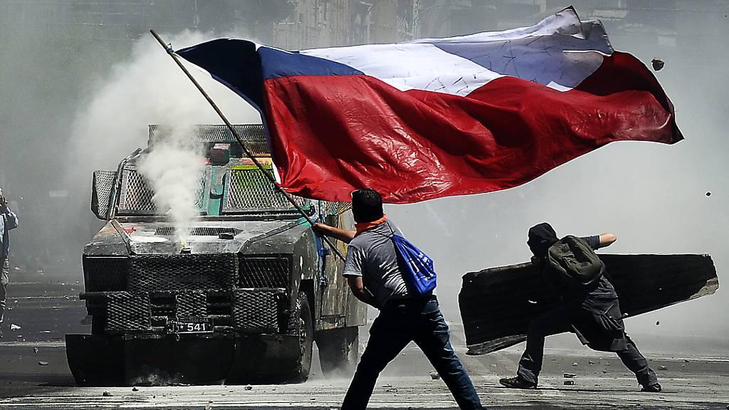 ARCHIV - Ein Demonstrant schwenkt eine große chilenische Flagge vor einem Wasserwerfer während eines Protests gegen soziale Ungleichheit und gegen die Regierung von Pinera im Oktober 2019. Foto: Pablo Ovalle Isasmendi/Agencia Uno/dpa