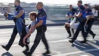 """Aktivisten der Bewegung """"Extinction Rebellion"""" gegen die Klimakrise wurden am 20. September von der Polizei weggetragen und in Gewahrsam genommen, nachdem sie eine zentrale Brücke in Lausanne blockiert hatten. (Archivbild)."""
