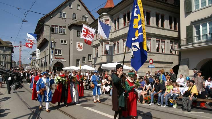 Die Hohe Fraumünsterfrau Susann Pflüger (hinter dem Fahnenträger, in Weiss) mit der Gesellschaft zu Fraumünster beim Umzug am Limmatquai.