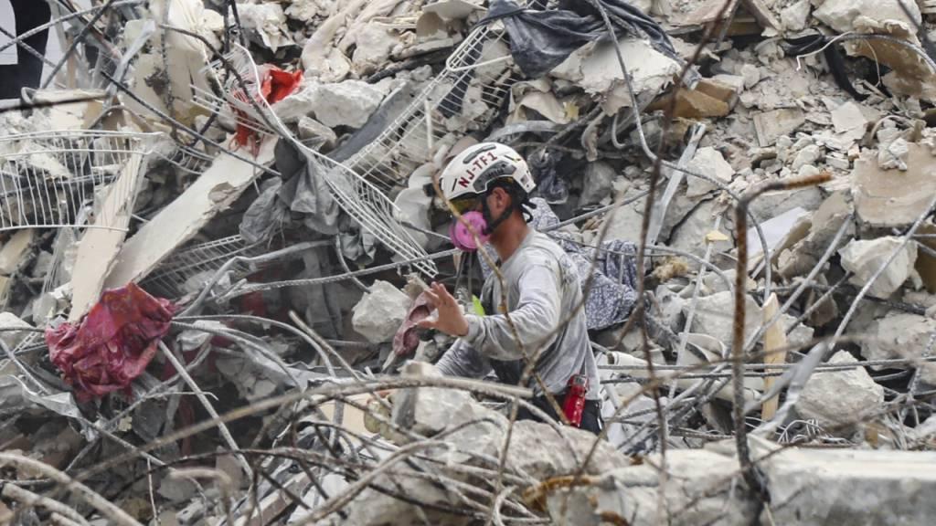 Rettungskräfte arbeiten sich durch die Trümmern des teilweise eingestürzten Wohnkomplexes. Foto: Al Diaz/Miami Herald/AP/dpa