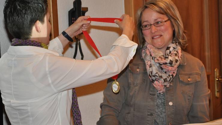 Vorstandsmitglied Fränzi Heller übergibt der abtretenden Präsidentin Ruth Bader eine Goldmedaille.