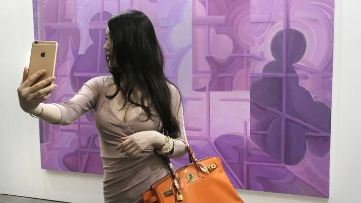 Kunst als Selfie-Hintergrund: Die junge Frau fotografiert sich an der Art Basel Hongkong vor einem Bild des chinesischen Künstlers Xu Xiaoguo Kong.