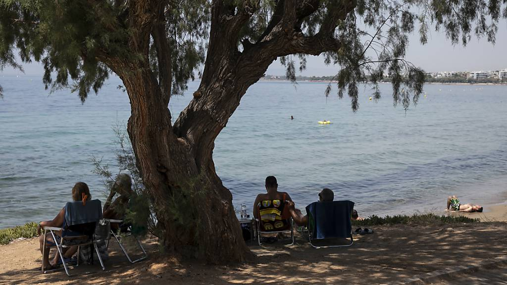 Besucher sitzen im Schatten unter einem Pinienbaum am Strand des Vororts Kavouri südwestlich von Athen. Foto: Yorgos Karahalis/AP/dpa