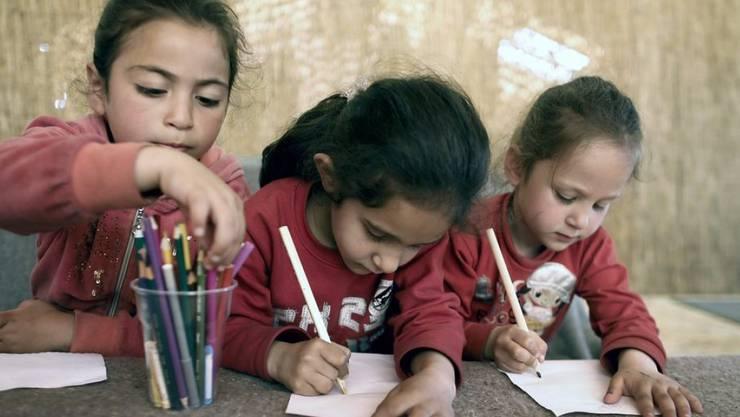 Flüchtlingskinder im griechischen Flüchtlingslager Idomeni während einer Lektion Zeichnen. Bis Ende Oktober soll allen mehr als 20'000 minderjährigen Flüchtlingen des Landes der Schulbesuch ermöglicht werden. (Archiv)