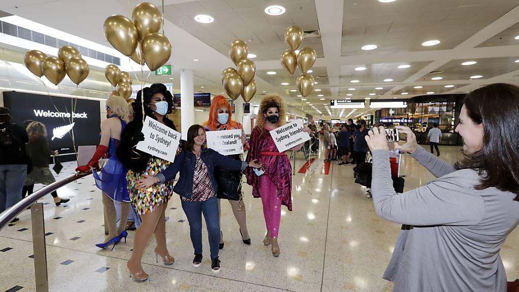 Eine Passagierin aus Neuseeland (M) stellt sich mit sich für ein Foto mit Drag Queens, die sie am Flughafen Sydney begrüßen, auf. Erstmals seit Beginn der Corona-Pandemie können Menschen in Neuseeland und Australien ab dem 19. April wieder zwischen beiden Ländern reisen.