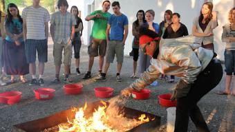 Die Künstlerin bearbeitet die gebrannten Rakuschalen aus dem 1000 Grad heissen Ofen mit Holzspänen. Foto: cme