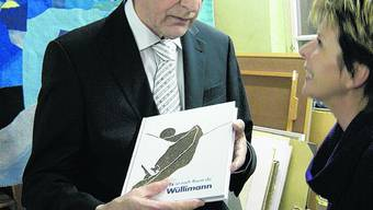 Im Atelier: Peter Wullimann, der eine Ausgabe seines Buches in den Händen hält, im Gespräch mit seiner Frau Mila.