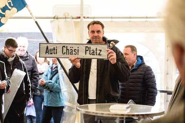 """Roger Blanc zeigt das Schild für den """"Auti Chäsi Platz""""."""