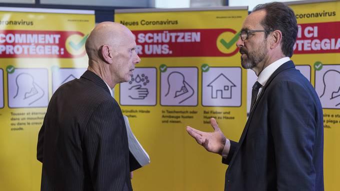Mit gelben Flyern wollen Daniel Koch, Leiter übertragbare Krankheiten beim Bundesamt für Gesundheit (links), und BAG-Leiter Pascal Strupler (rechts) auf die Hygienemassnahmen während des Corona-Virus aufmerksam machen.