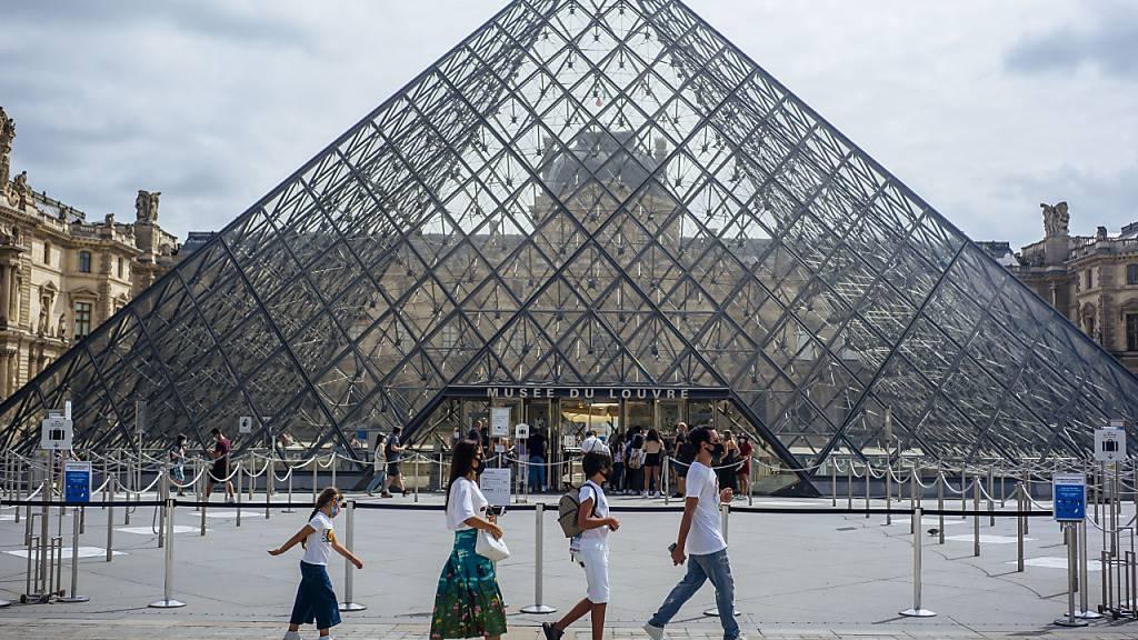 ARCHIV - Eine Familie mit Schutzmasken geht am Louvre vorbei. (zu dpa «Corona-Krise: Frankreich kommt seinen großen Museen zu Hilfe») Foto: Kamil Zihnioglu/AP/dpa