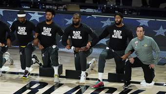 Die Spieler der Los Angeles Lakers und ihr Coach Frank Vogel knien während der Nationalhymne nieder. Danach nehmen sie nach einer mehrtägigen Pause das Wettkampfgeschehen wieder auf.