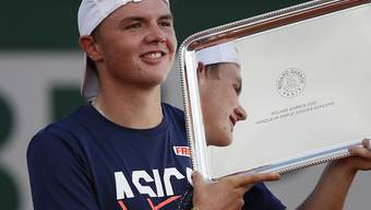 Dominic Stricker zeigt seine French-Open-Trophäe