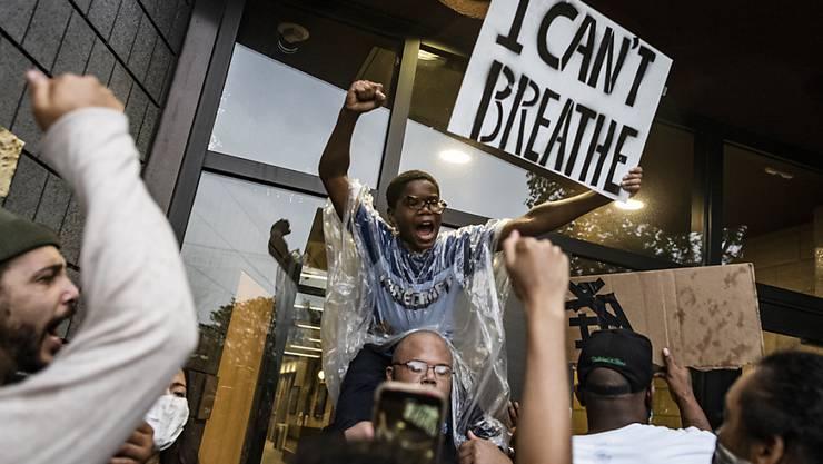 """Demonstranten versammeln sich auf einem Polizeirevier und fordern mit einem Plakat mit der Aufschrift """"I can't breathe"""" (dt. Ich kann nicht atmen) Gerechtigkeit für einen Mann afroamerikanischer Abstammung, der nach der Festnahme durch die Polizei verstarb. Der weiße Polizist kniete auf dem Hals des Mannes, welcher mehrmals darauf aufmerksam machte, dass er nicht atmen könne. Der Mann starb später im Krankenhaus. Foto: Richard Tsong-Taatarii/Star Tribune/AP/dpa"""