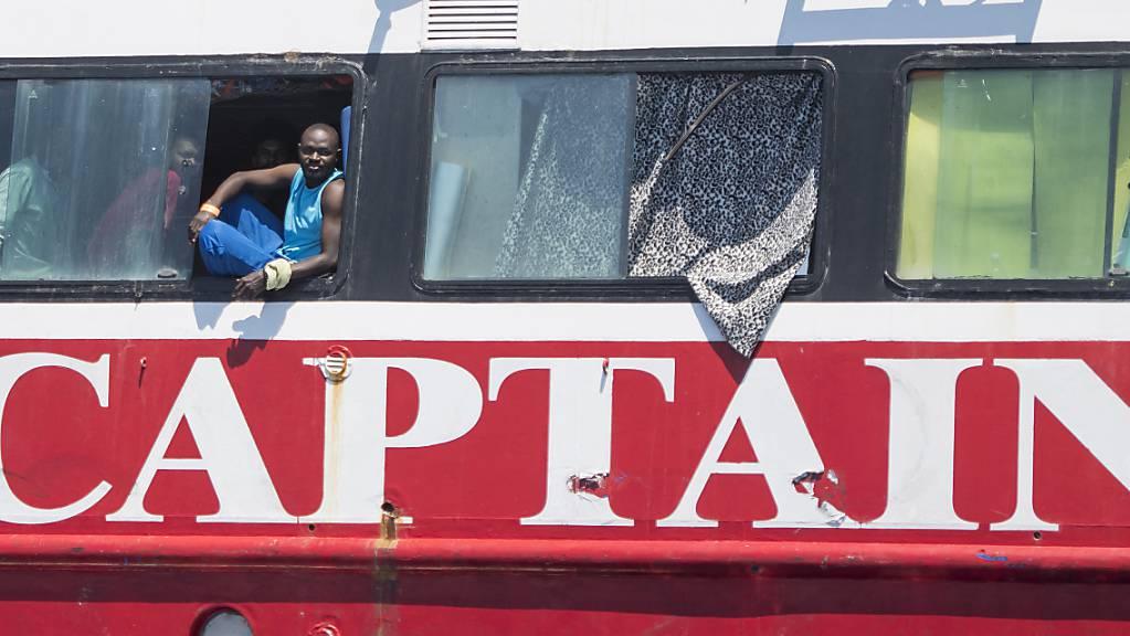 Migranten blicken aus dem Fenster an Bord eines Touristenbootes etwa 20 Kilometer vor Malta.