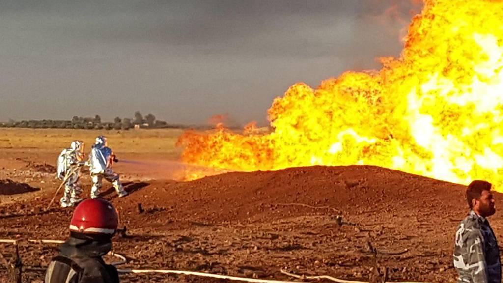 HANDOUT - Auf diesem Foto, das von der offiziellen syrischen Nachrichtenagentur SANA veröffentlicht wurde, löschen syrische Feuerwehrleute die Flammen einer Gaspipeline, die von einer Explosion zwischen den nordöstlichen Damaszener Vororten Adra und Dumair getroffen wurde. Foto: SANA/AP/dpa - ACHTUNG: Nur zur redaktionellen Verwendung und nur mit vollständiger Nennung des vorstehenden Credits
