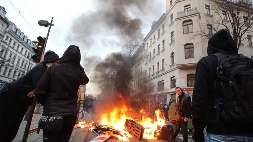 Linke Demonstranten vor einer brennenden Barrikade am Samstag in Leipzig.