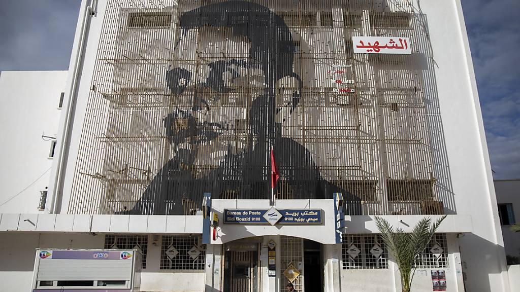 ARCHIV - Auf der Fassade eines Postamtes in der tunesischen Kleinstadt Sidi Bouzid ist das Gesicht des tunesischen Gemüsehändlers Mohammed Bouazizi abgebildet, der sich am 17. Dezember 2010 selbst anzündete - aus Verzweiflung über seine Lebenslage und die Willkür der Behörden. Foto: Riadh Dridi/AP/dpa