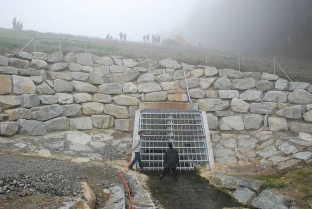 Hier fliesst der Erusbach unter dem Schutzdamm durch ein Gitter hält Holz und Geschiebe zurück