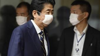 Shinzo Abe, Ministerpräsidenten von Japan, kommt zu einer Pressekonferenz und trägt einen Mundschutz. Japan hebt den Corona-Notstand in den meisten Landesteilen vorzeitig auf. Abe gab diese Entscheidung nach Beratungen mit Experten bekannt. Ausgenommen sind städtische Großräume wie Tokio und Osaka. Foto: Akio Kon/POOL Bloomberg/dpa