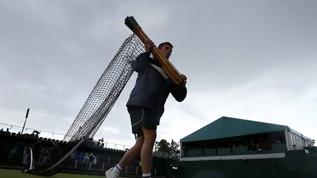 Ein oft gesehenes Bild in dieser Woche: Helfer rollen die Netze ein, um die Plätze bei einsetzendem Regen abzudecken