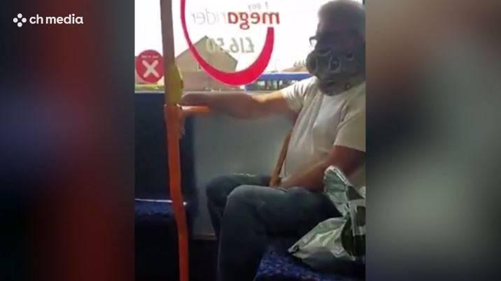 Mann benutzt lebende Schlange als Mundschutz im Bus