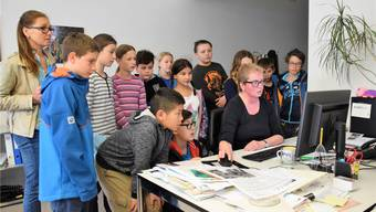 Die Fünftklässler von Lehrerin Barbara Gabathuler (links) schauen az-Ressortleiterin Claudia Meier an ihrem Arbeitsplatz über die Schulter. mhu